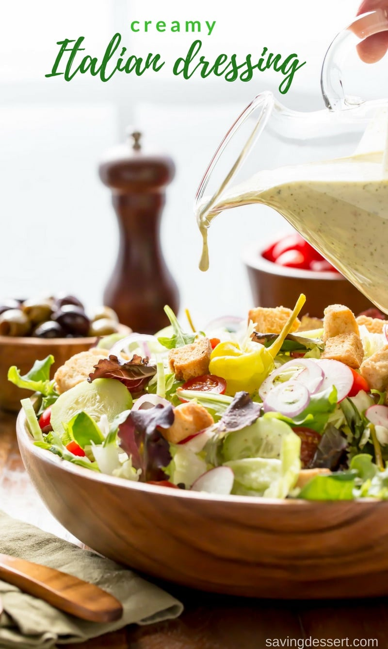 A wooden bowl of salad drizzled with creamy Italian dressing