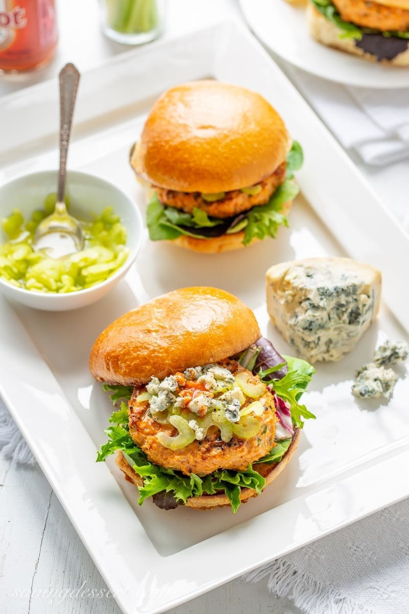 Buffalo flavored chicken burgers on a bun with celery and crumbled blue cheese