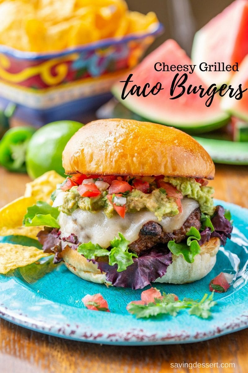 A cheesy Taco burger with guacamole, lettuce, chips and lime