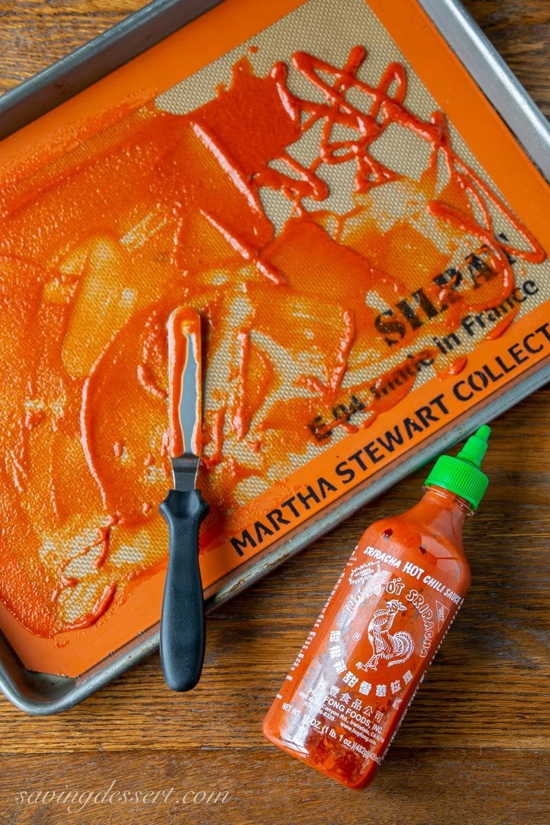 Sriracha Sauce spread on a silpat mat on a rimmed baking sheet