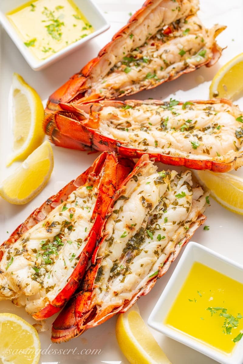 4 grilled lobster tails on a platter with lemon slices and melted butter