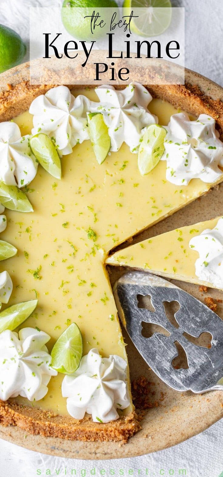 A sliced key lime pie decorated with fresh key limes and whipped cream