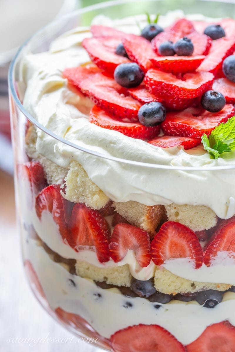A close up of a trifle bowl with mixed berries, pound cake and vanilla custard