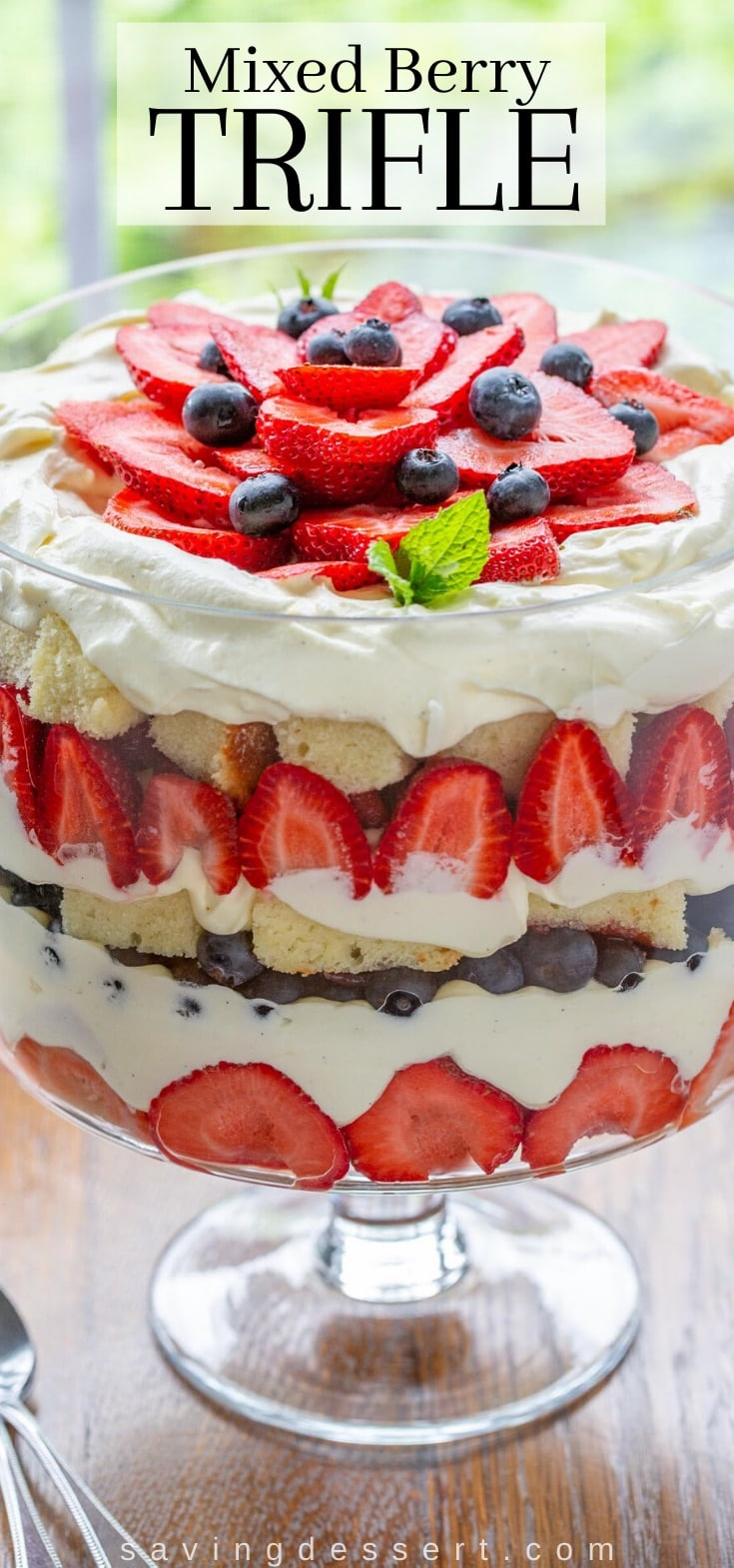 A trifle bowl filled with vanilla creamy, blueberries, strawberries and pound cake