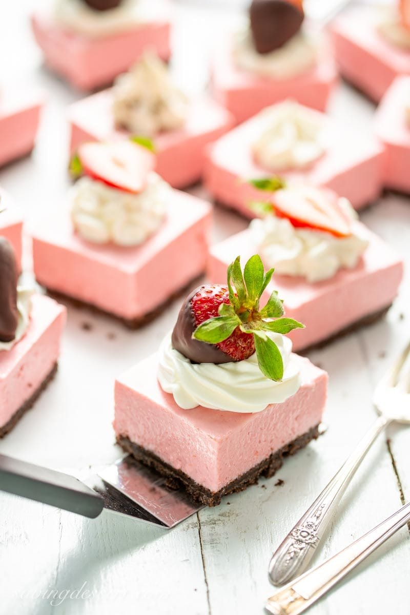 Strawberry Cheesecake Bars decorated with whipped cream, sliced strawberries and chocolate covered strawberries.