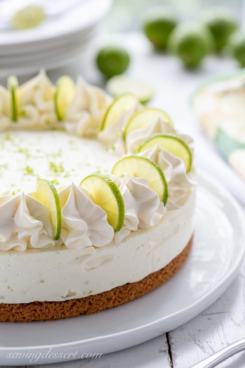Key Lime Icebox Cheesecake with whipped cream and key lime wedges