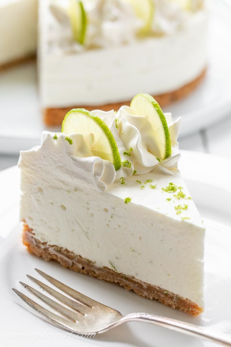 A slice of Key Lime Icebox Cheesecake decorated with cream cheese whipped cream, key lime slices and key lime zest