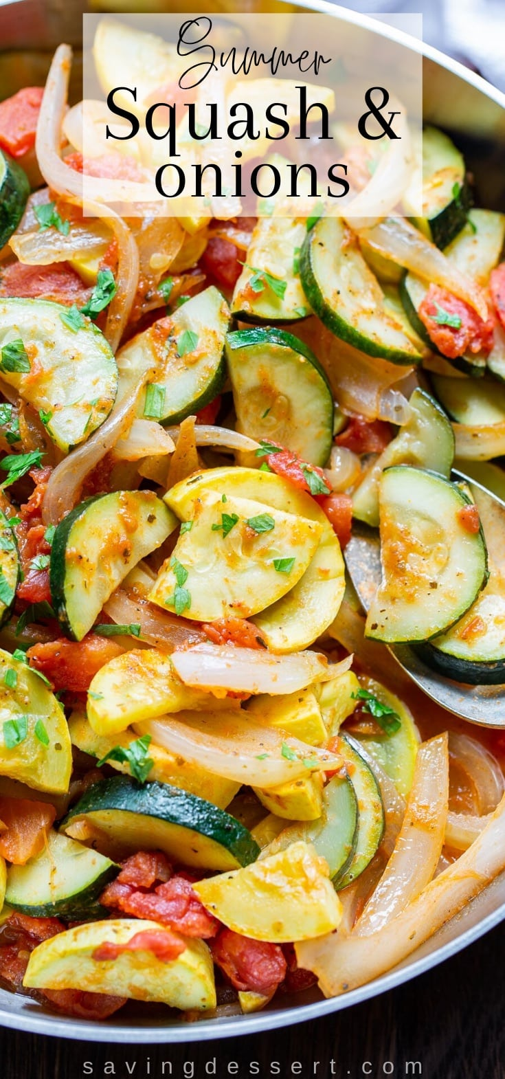 an overhead shot of a skillet filled with yellow squash, zucchini, onions and tomatoes