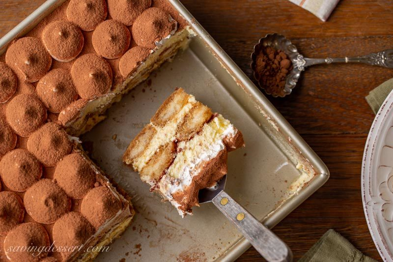 A pan of classic Tiramisu topped with mounds of whipped cream