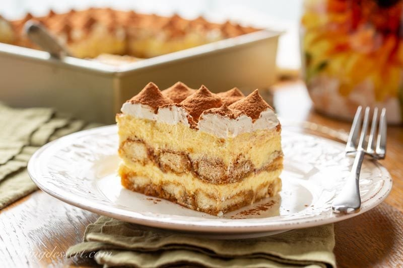 Side view of a slice of Tiramisu on a plate with a fork