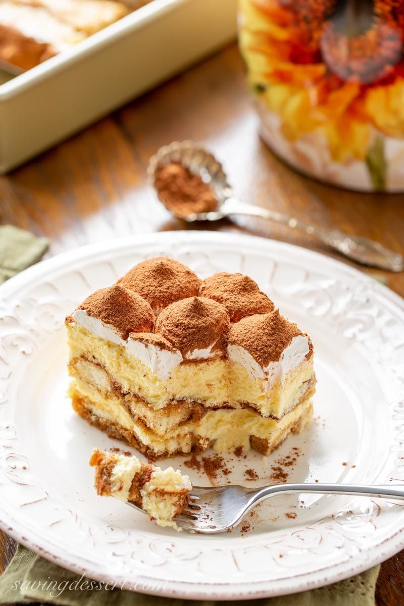 A piece of Tiramisu dusted with cocoa with a bite taken out with a fork