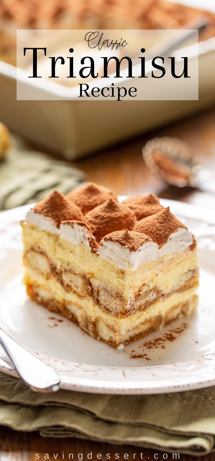 A slice of classic Tiramisu with mounds of whipped cream on top dusted with cocoa