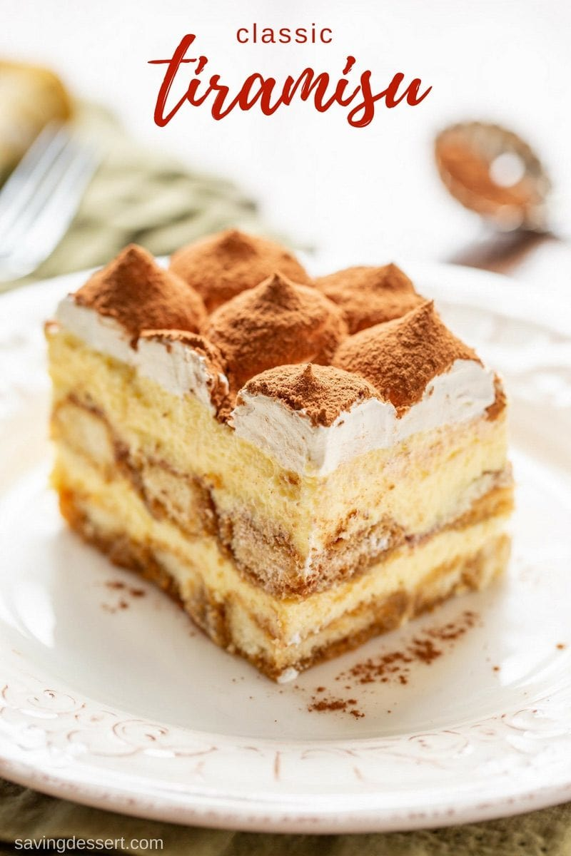 A close up of a slice of Tiramisu dusted with cocoa powder