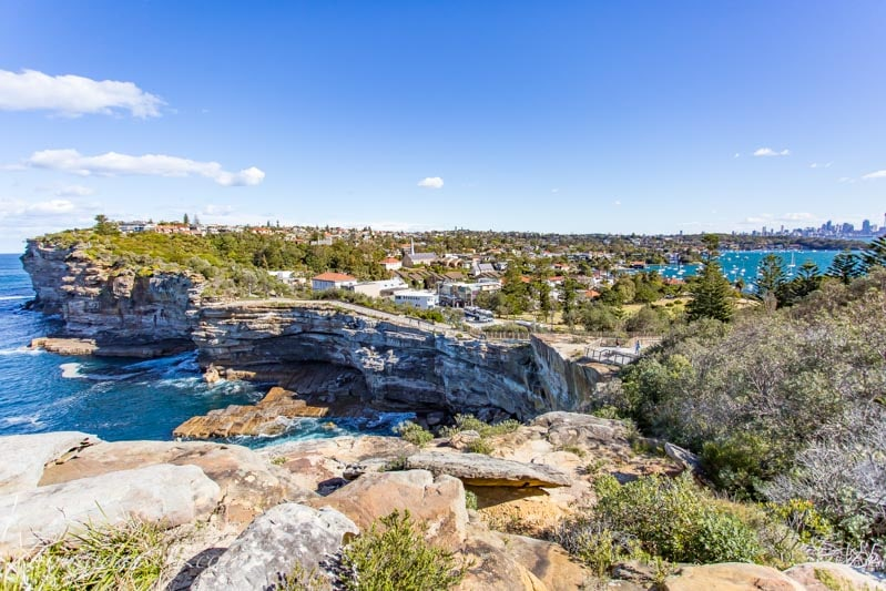 A view of Watsons Bay community from the Gap, with views of the cliffs and downtown Sydney