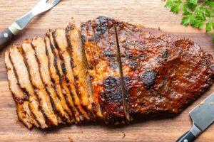 Thin sliced BBQ'd beef brisket on a cutting board