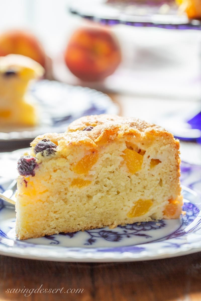 A big slice of fresh peach breakfast cake with a few blueberries