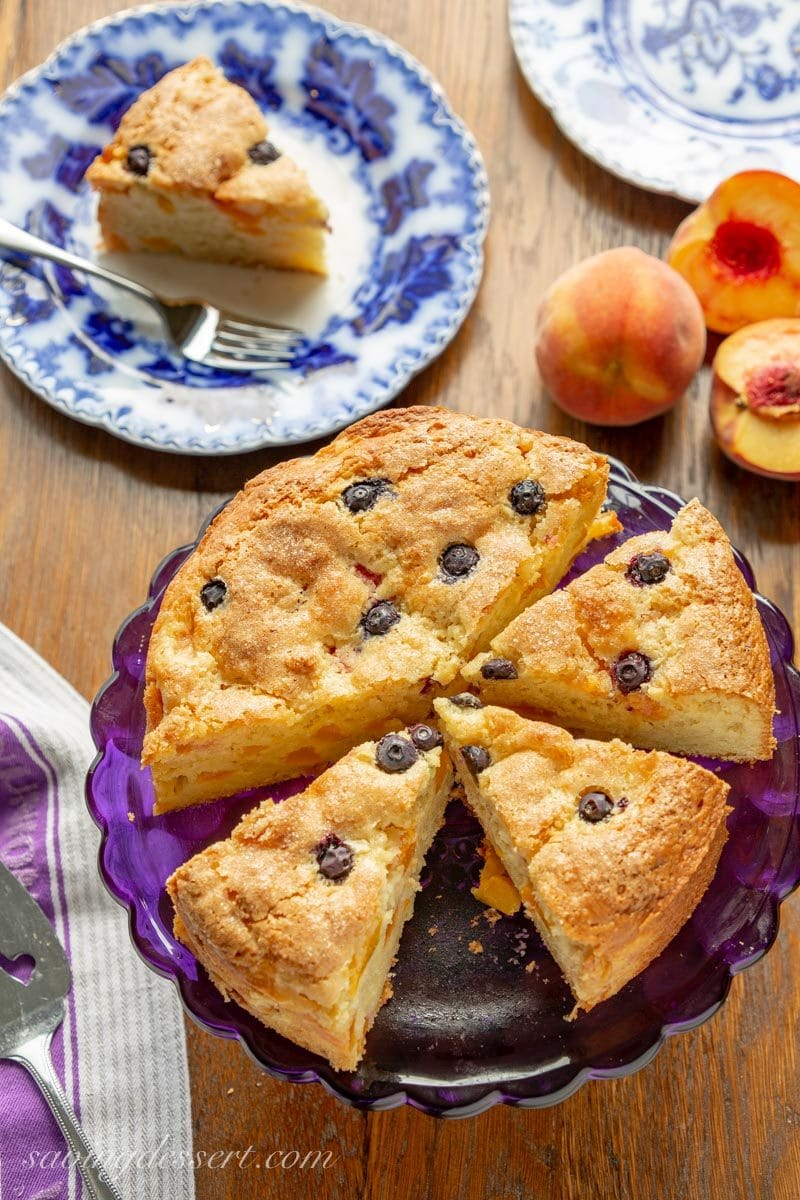 Sliced fresh peach breakfast cake with blueberries