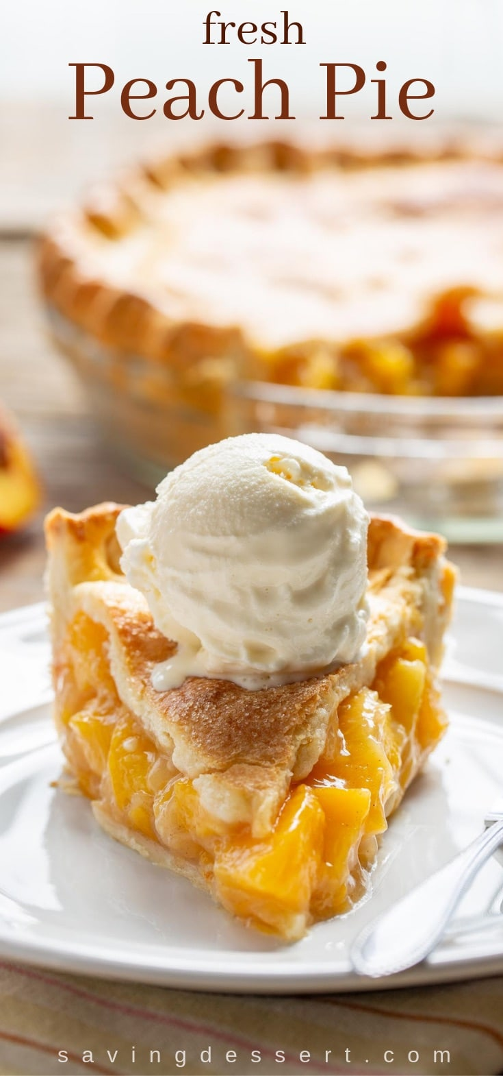 A thick slice of fresh peach pie topped with a scoop of vanilla ice cream
