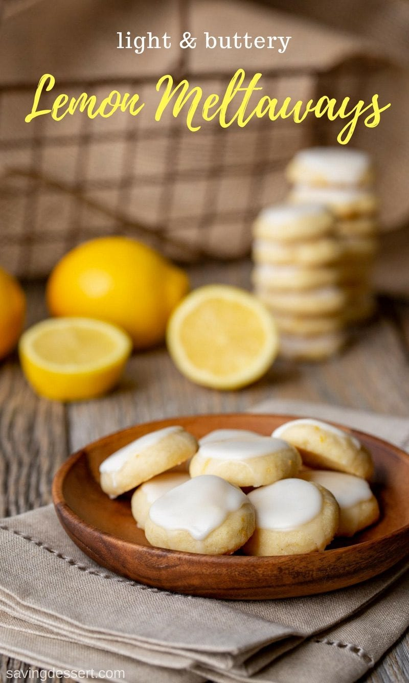 Lemon Meltaways on a plate with fresh lemons and a basket