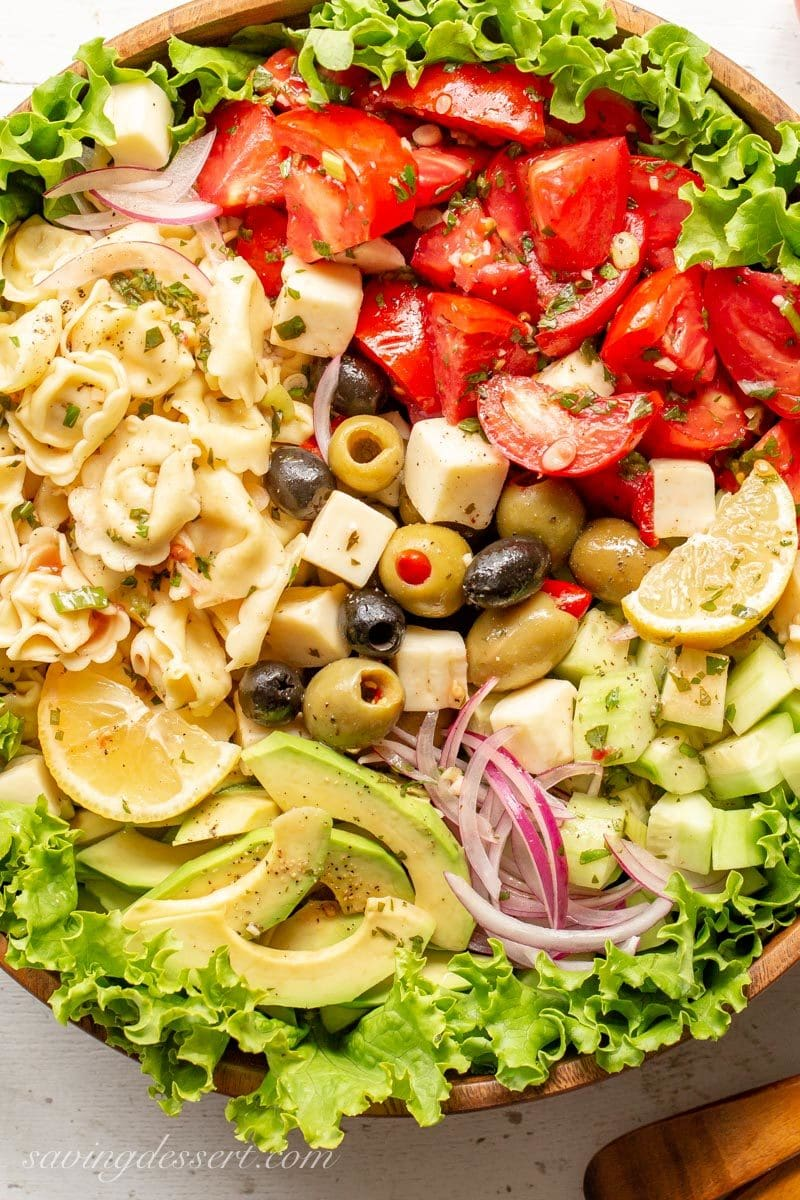 A large wooden bowl with Marinated Tomato & Tortellini Salad with cucumbers, onion, olives, avocado, cheese and fresh garden herbs.