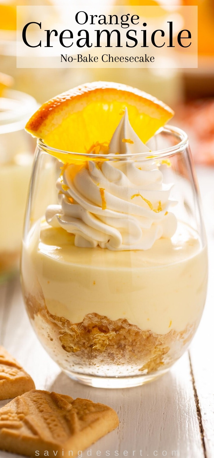 A small glass filled with orange creamsicle dessert topped with whipped cream and an orange slice