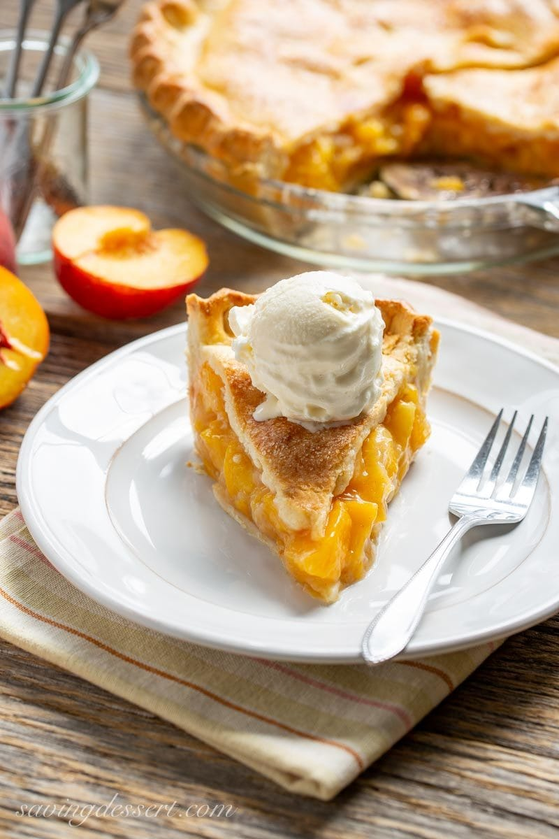 A slice of Old Fashioned Fresh Peach Pie with vanilla ice cream on top