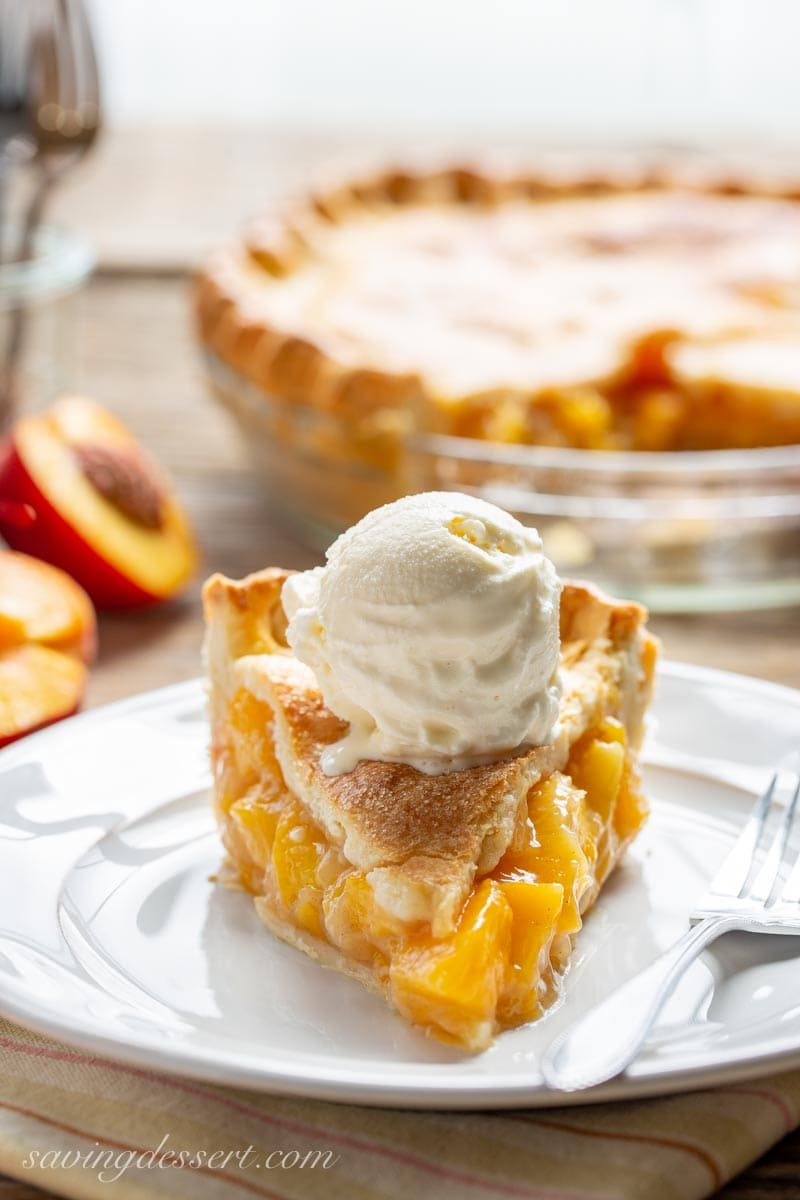 A slice of peach pie topped with a scoop of ice cream