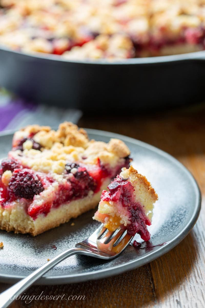 Cast iron skillet with plum blackberry bars and a shortbread crumble dough on top