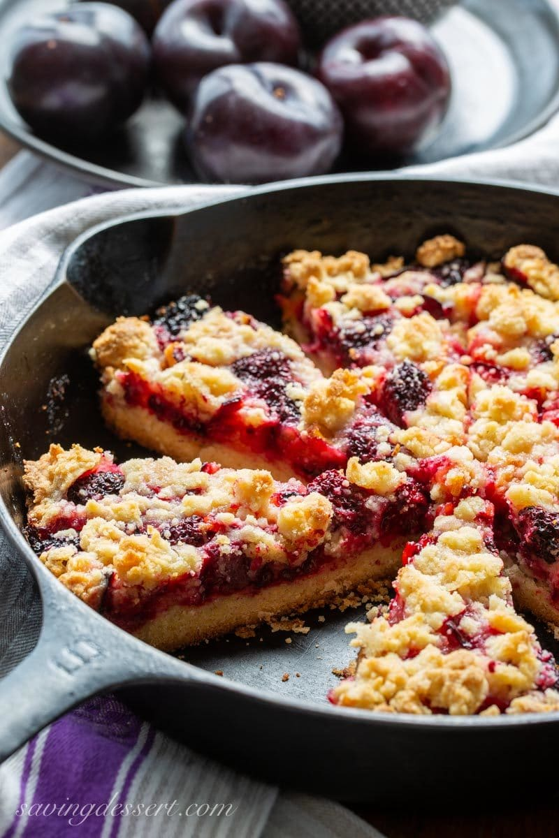 Cast iron skillet with sliced plum blackberry bars and a shortbread crumble dough on top