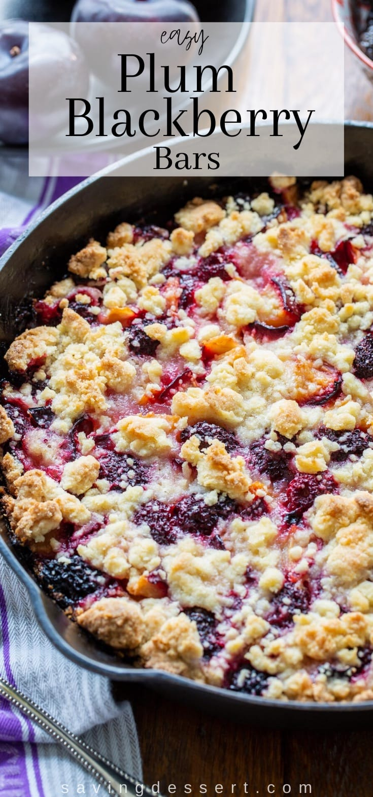 A cast iron skillet filled with blackberry plum crumble bars