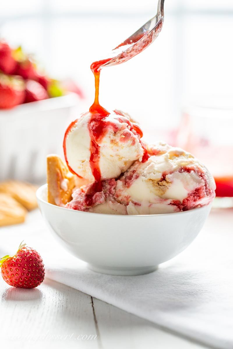 Strawberry Shortcake Ice Cream with a drizzle of strawberry sauce and shortbread cookies.