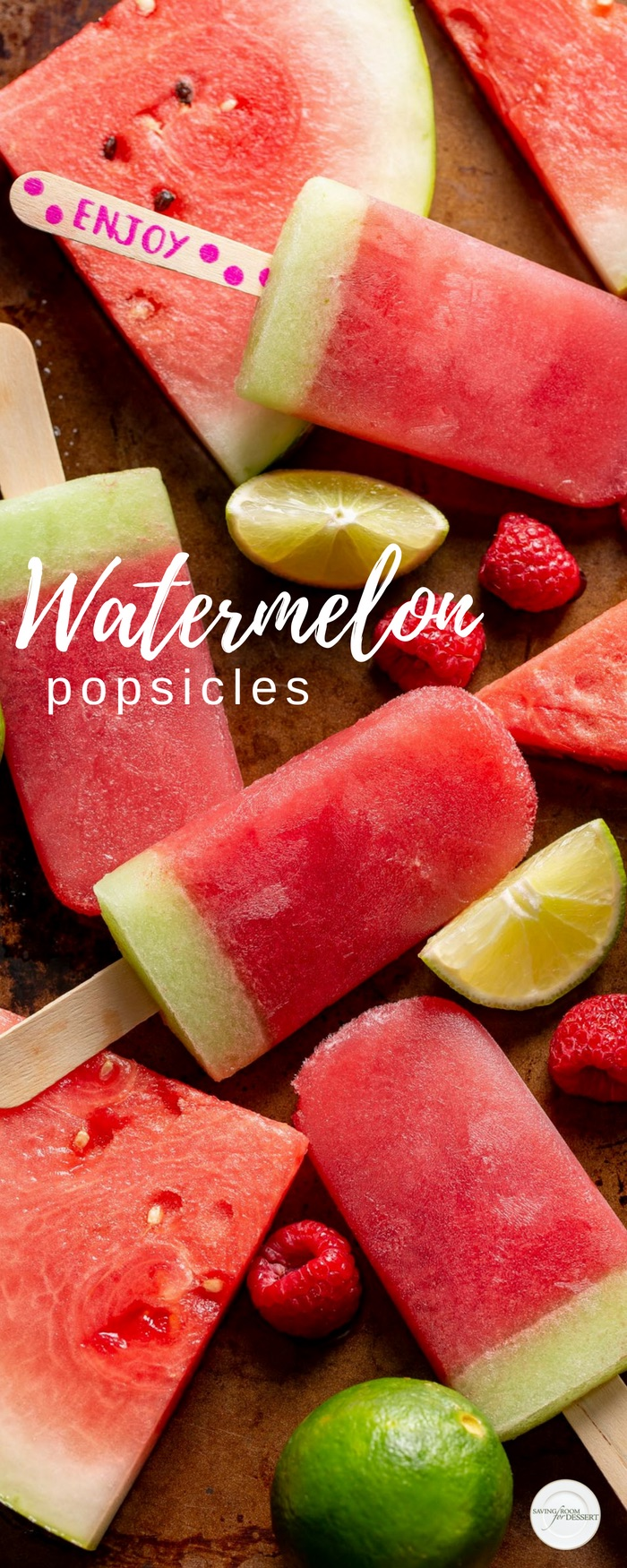 Watermelon popsicles scattered on a baking tray with raspberries, lime wedges and pieces of watermelon