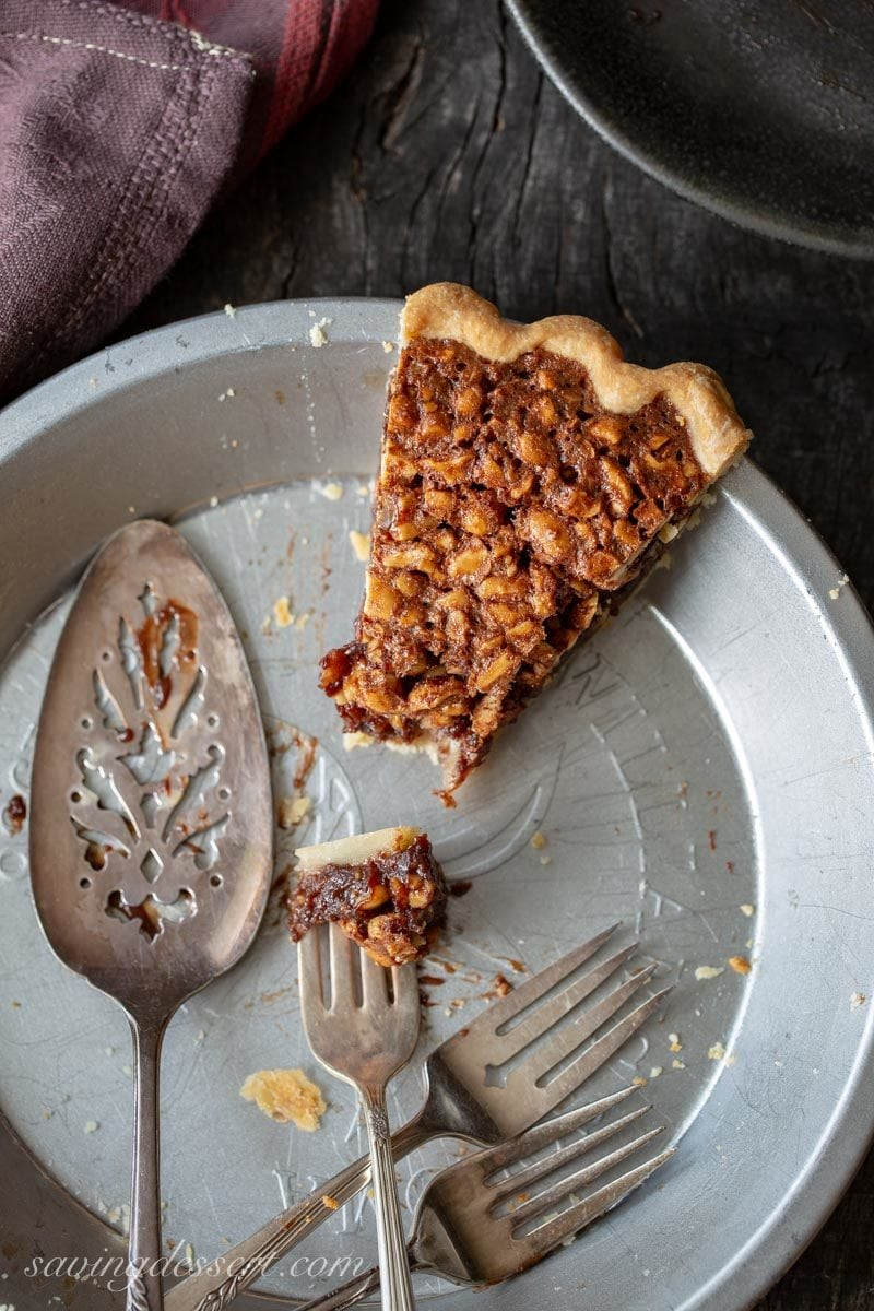 The last slice of chocolate peanut pie in the pie plate with a pie server and extra forks
