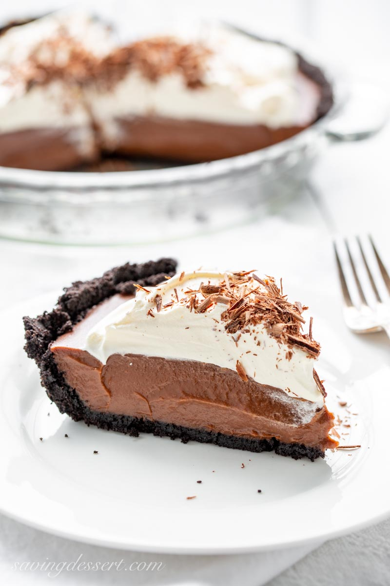 A slice of chocolate pie with a chocolate cookie crust, topped with whipped cream and chocolate shards