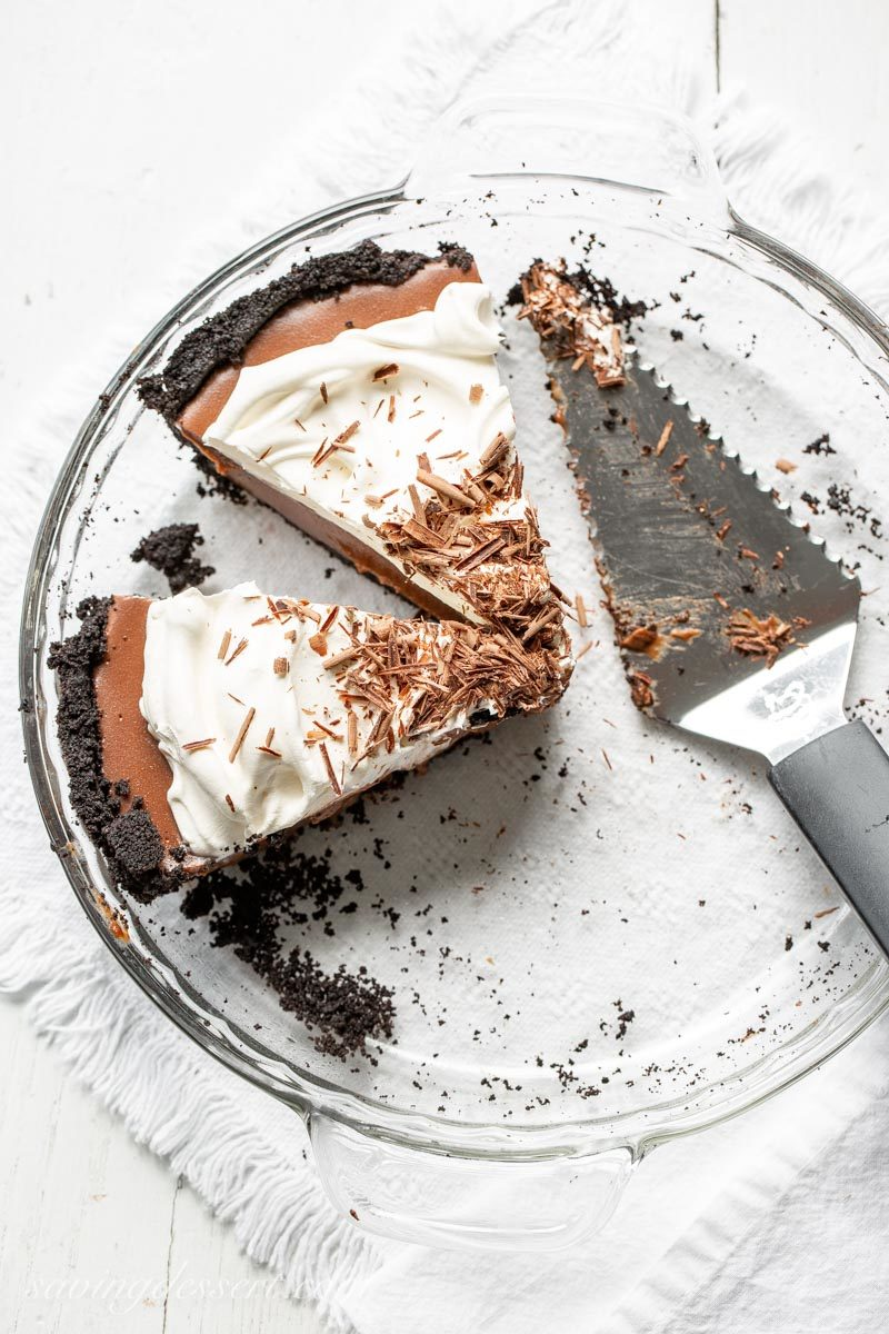 two slices of Double Chocolate Cream Pie with a chocolate cookie crumb crust, whipped cream and chocolate shavings on top
