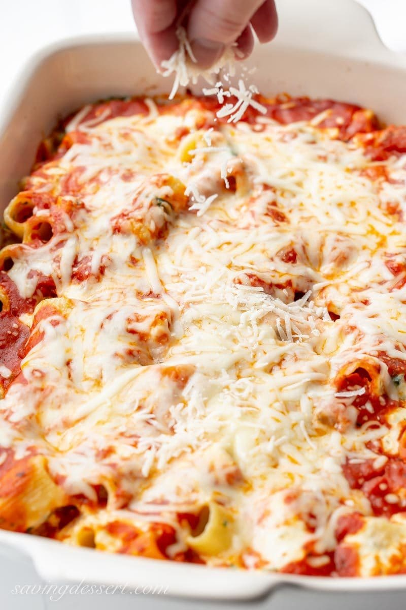 A large casserole dish with ricotta and spinach pasta bake, sprinkled with fresh grated Parmesan cheese.