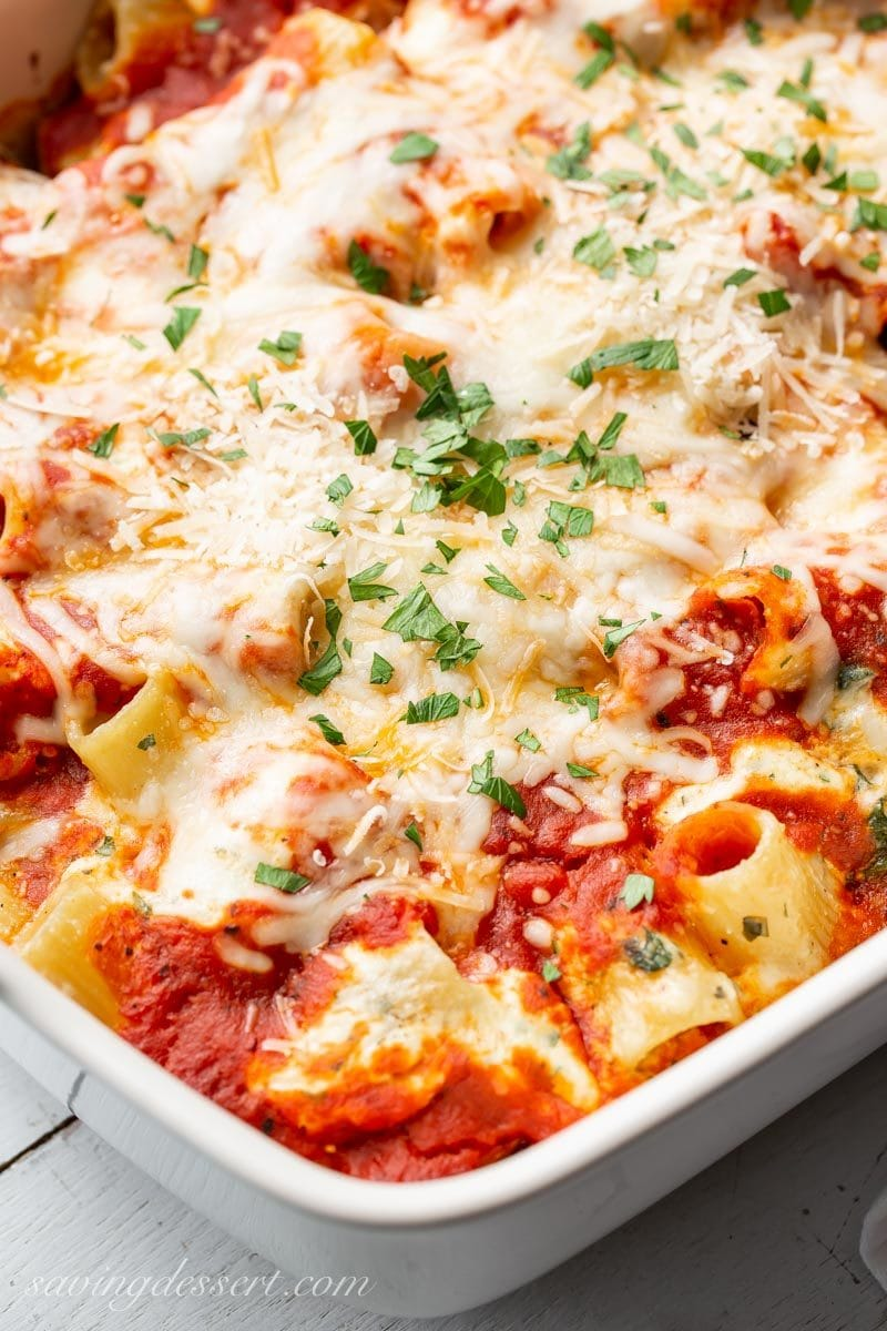 A large casserole of Ricotta Pasta Spinach Bake topped with cheese and parsley