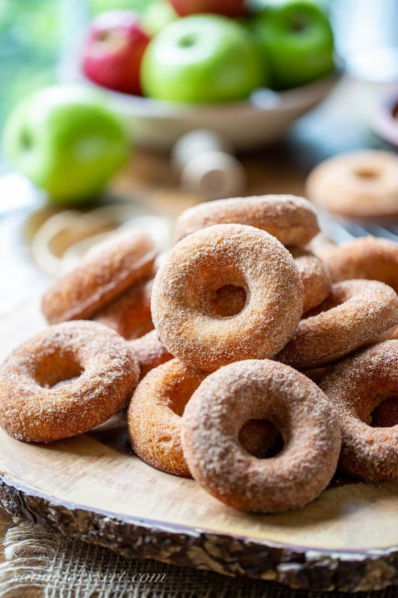 a pile of baked Apple Cider Doughnuts coated in cinnamon and sugar