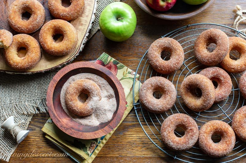 Baked apple cider doughnuts on a rack, board and one in a bowl tossed with a cinnamon sugar mixture