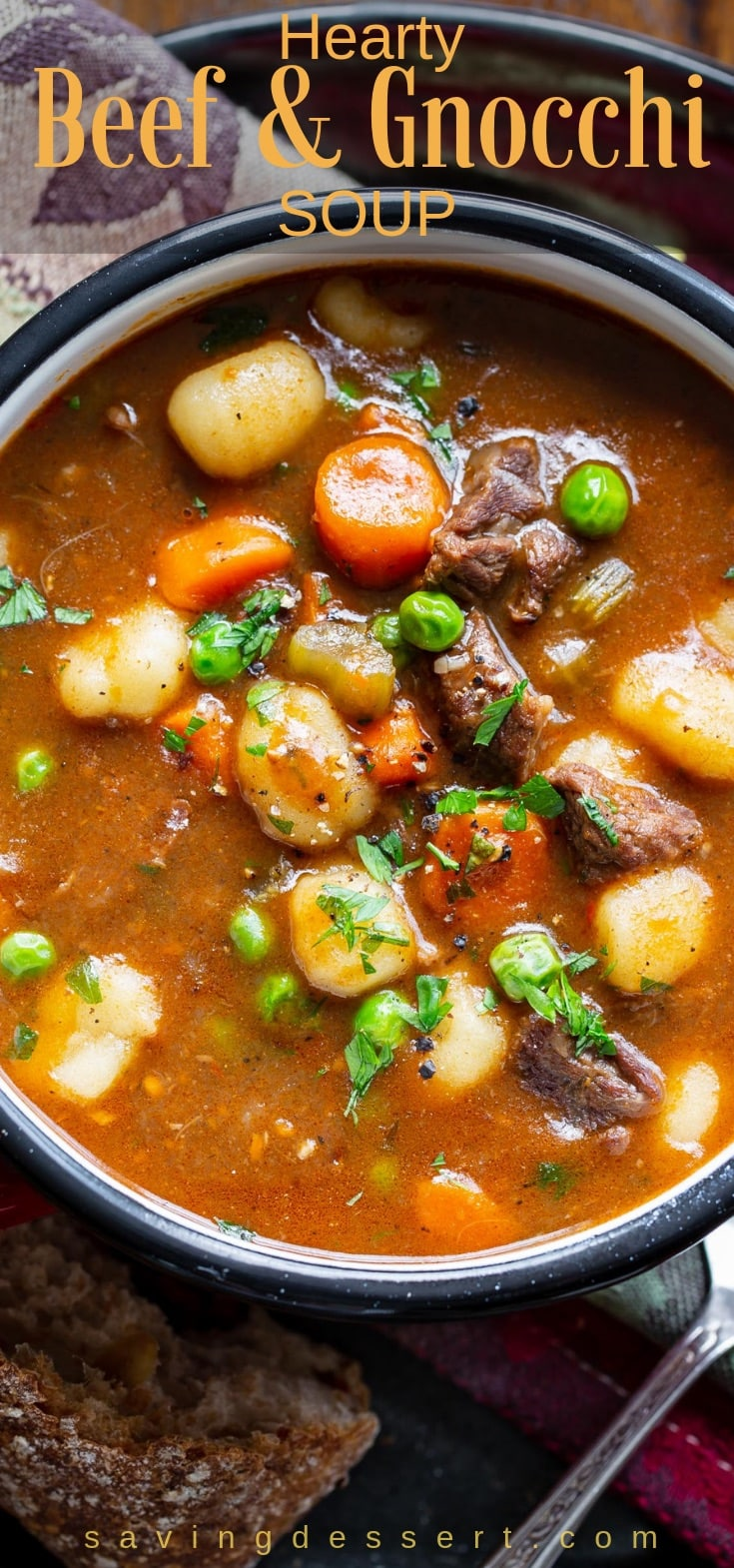 A bowl of hearty beef and gnocchi soup with peas and carrots garnished with parsley