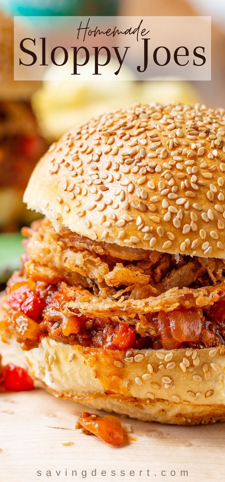 A close up of a sloppy joe sandwich topped with crispy onions on a toasted sesame seed bun