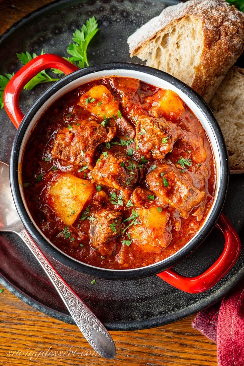 A bowl of Hungarian style Beef Goulash served with bread and topped with chopped fresh parsley leaves