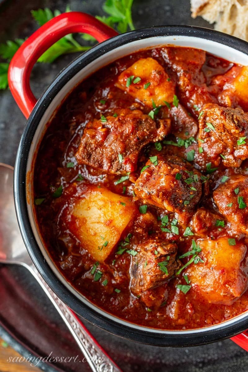 a close up of a bowl of Hungarian Beef Goulash with potatoes and parsley