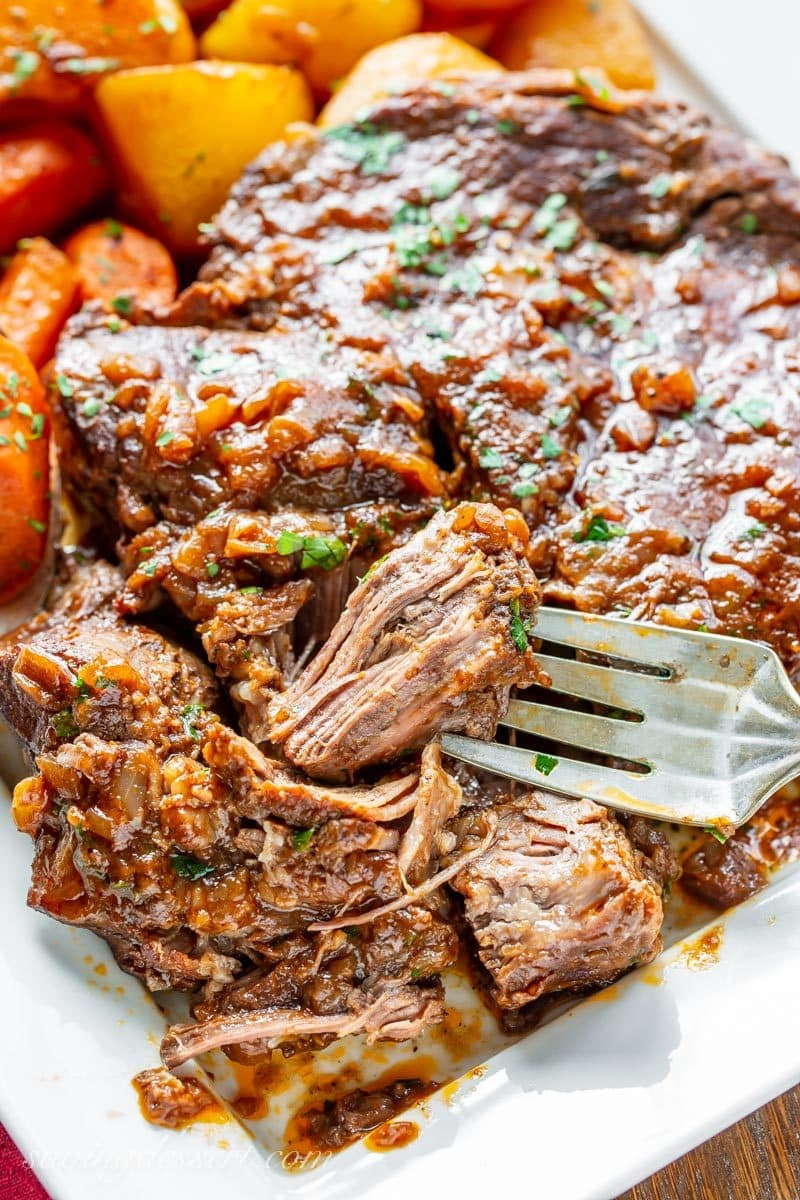 A platter with carrots potatoes and a fork tender oven braised pot roast