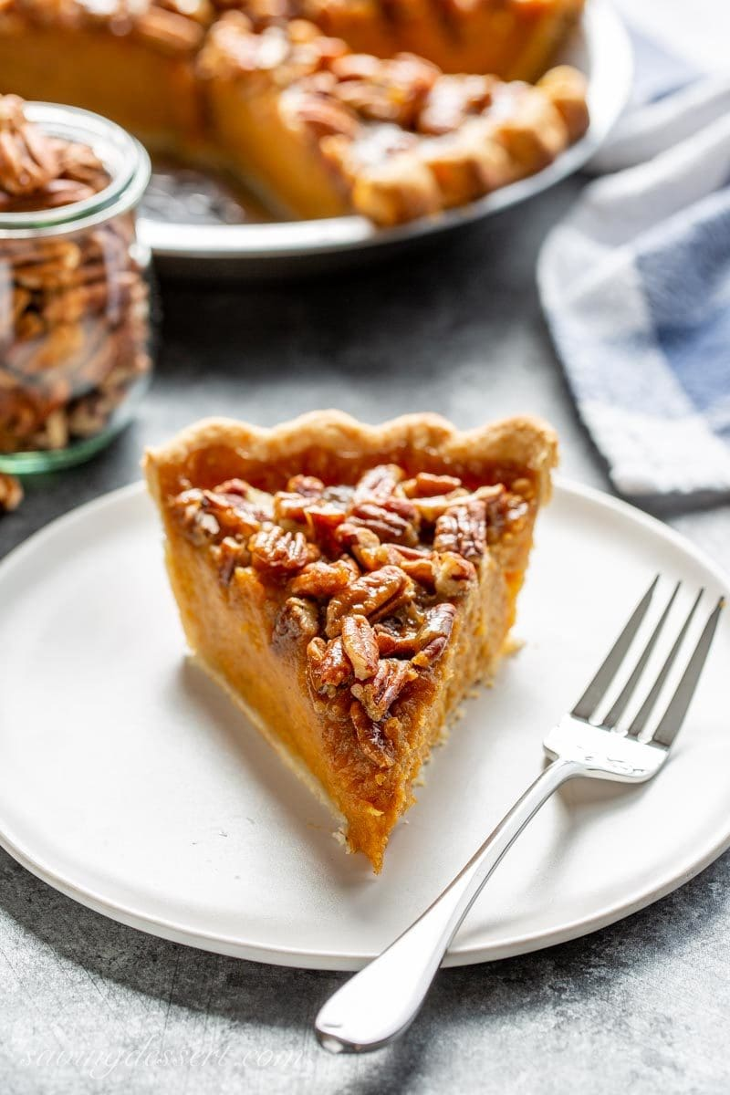 A slice of sweet potato pie with pecans and a caramel topping
