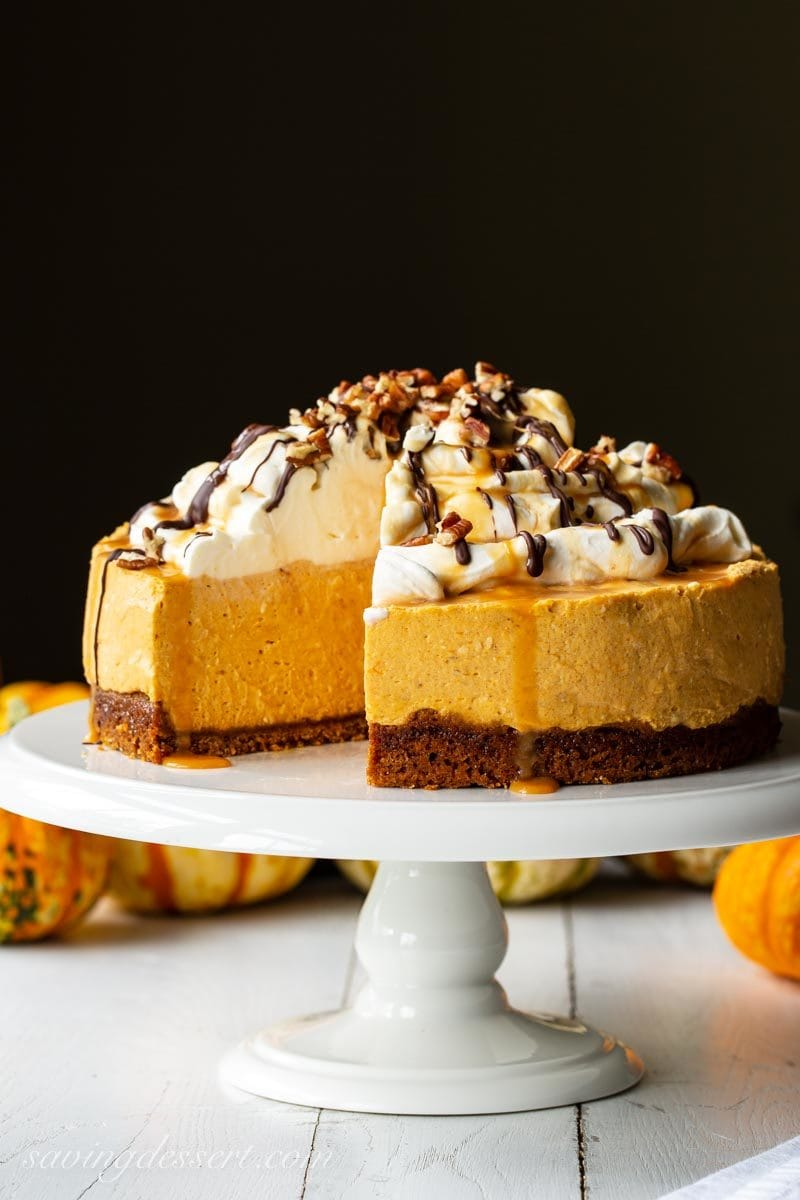 A sliced pumpkin cheesecake on a cake stand topped with whipped cream, chocolate and caramel