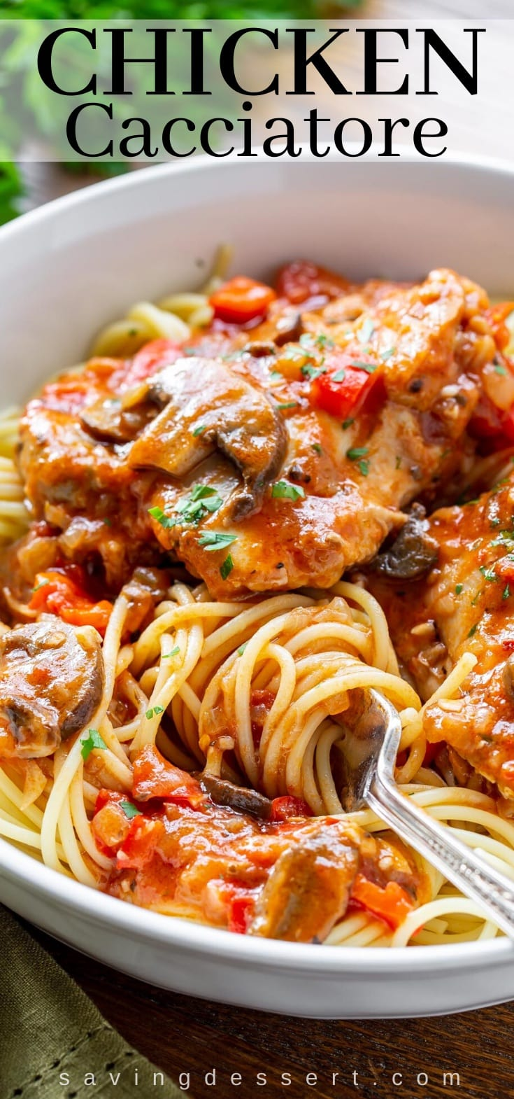 A bowl of spaghetti with chicken cacciatore on top with red peppers and mushrooms