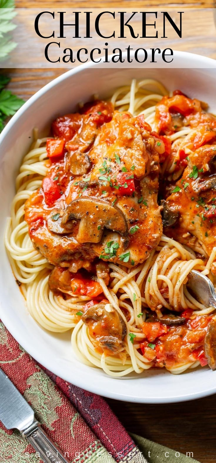 A bowl of spaghetti topped with chicken cacciatore and fresh parsley