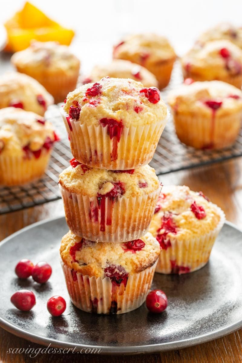 Three fluffy fresh Cranberry Orange Muffins stacked on a plate with fresh cranberries