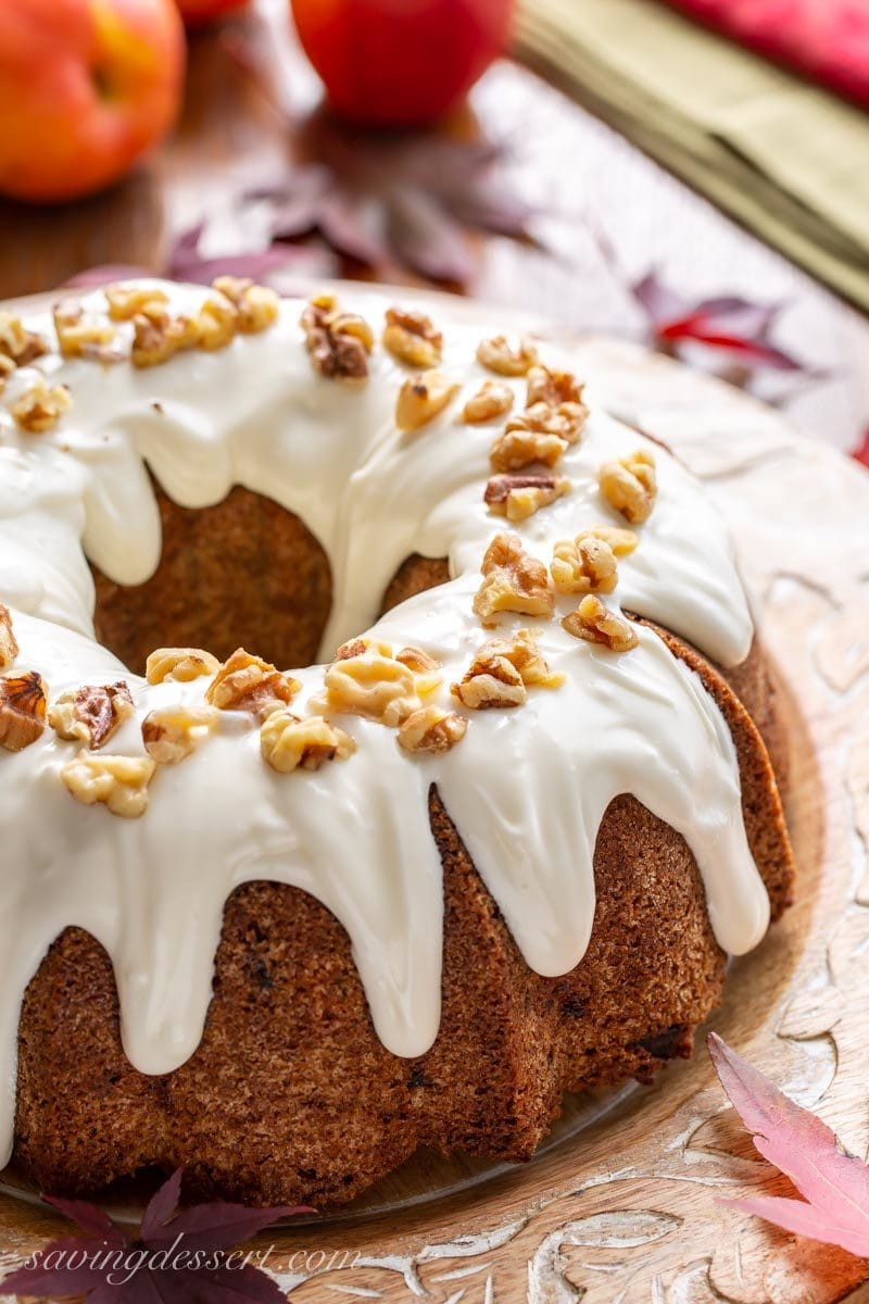 Fresh apple Bundt cake with cream cheese icing and walnuts